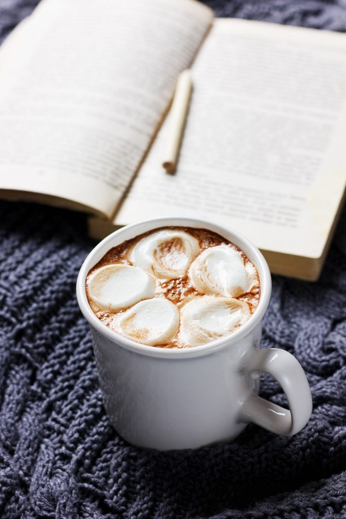 50571614 - vintage hot cup of cocoa or chocolate with marshmallows on a knitted sweater with book and pencil