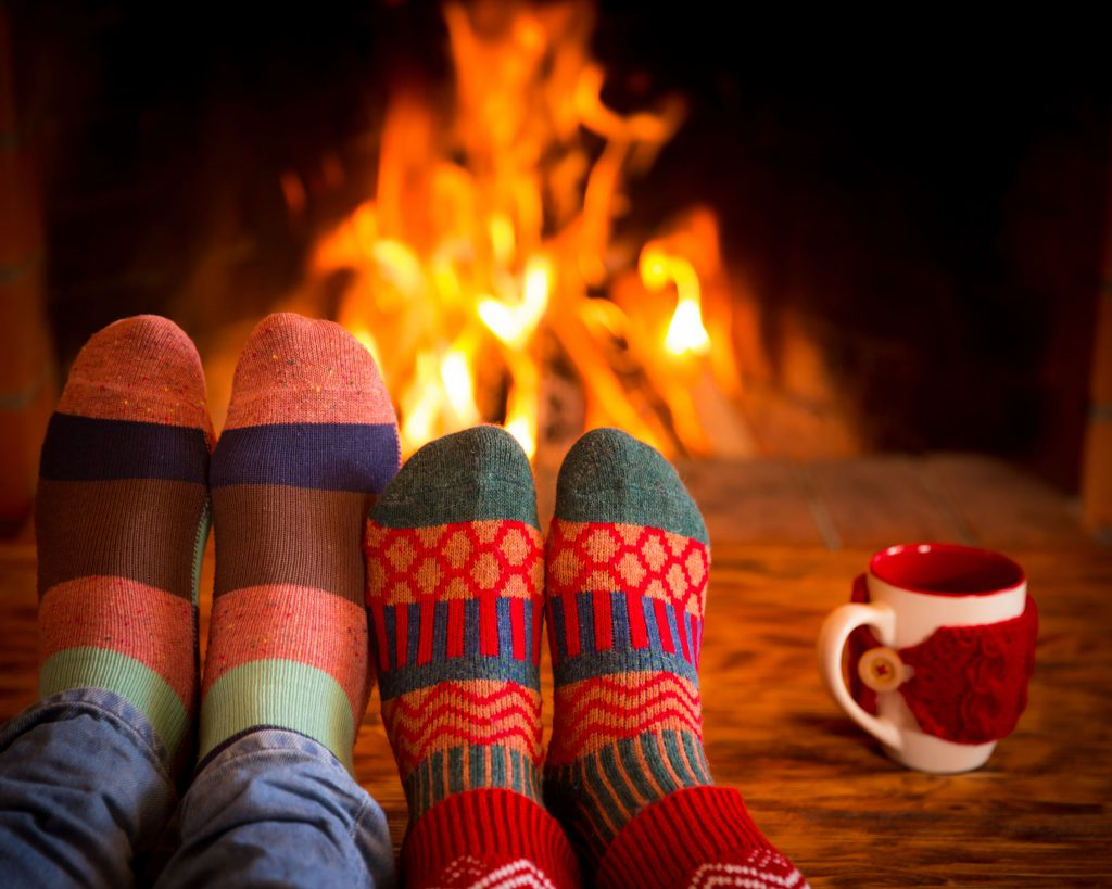 48002327 - couple relaxing at home. feet in christmas socks near fireplace. winter holiday concept